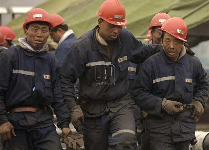 مجموعة من عمال أحد مناجم الفحم بمقاطعة شانسي شمال الصين ، يخرجون من المنجم بعد أن أغرقه الفيضان , 31 مارس 2010 , تحاول قوات الإنقاذ العثور على 150 عامل عالقين منذ 48 ساعة بالمنجم و لم يستطيعوا إنقاذهم بعد ، على الرغم أن عمليات الإنقاذ يشارك فيها ما يقرب من 1000 شخص . - صورة أرشيفية