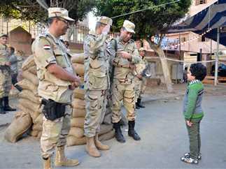 طفل يؤدي التحية العسكرية لرجال الجيش أمام إحدى لجان الاستفتاء ببورسعيد