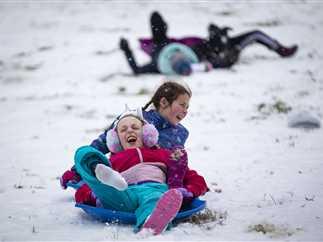 عاصفة ثلجية بالعاصمة الأمريكية واشنطن، والسكان يحتفلون بتساقطها بالتزلج ومعارك كرات الثلج